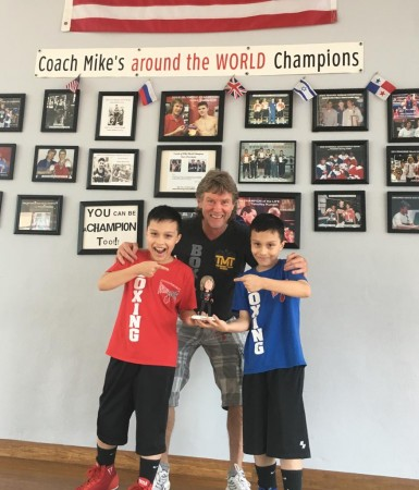 The twin brothers Joel and Jeremy Zhindon with a gift to boxing trainer Michael Kozlowski.
